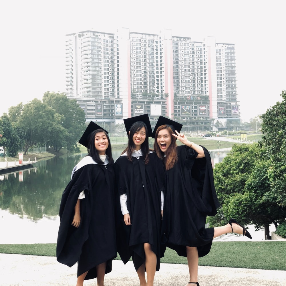 three women wearing academic gowns