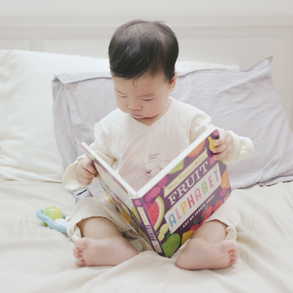 baby holding fruit alphabet book