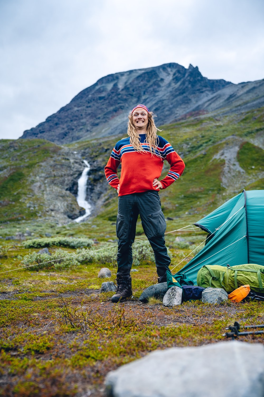 man in red and blue sweater beside camping tent