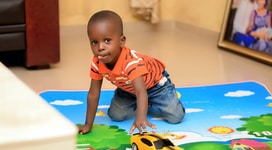 boy playing chevrolet camaro toy on floor