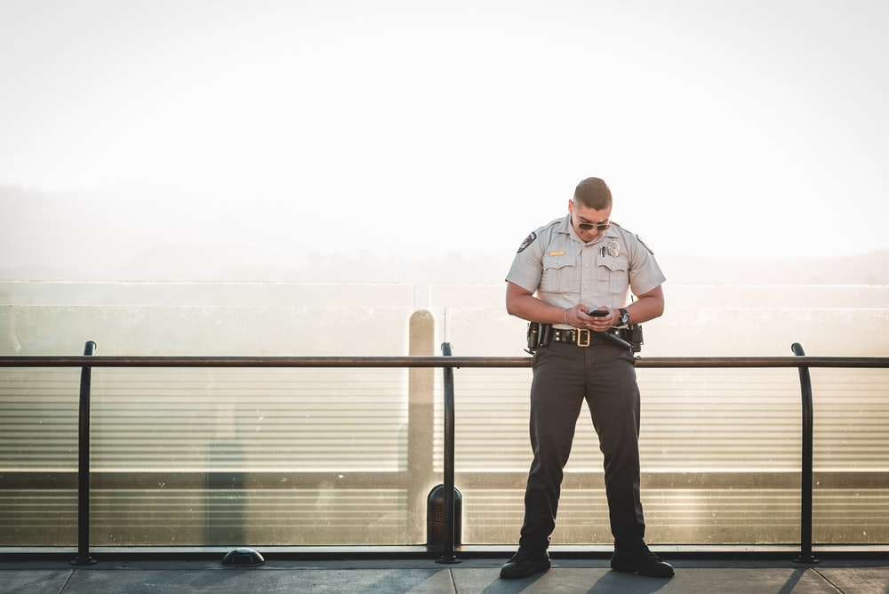 cop leaning on metal rail during a sunny day