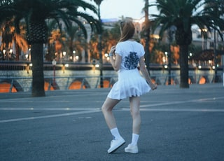 woman wearing white mini skirt standing on concrete surface