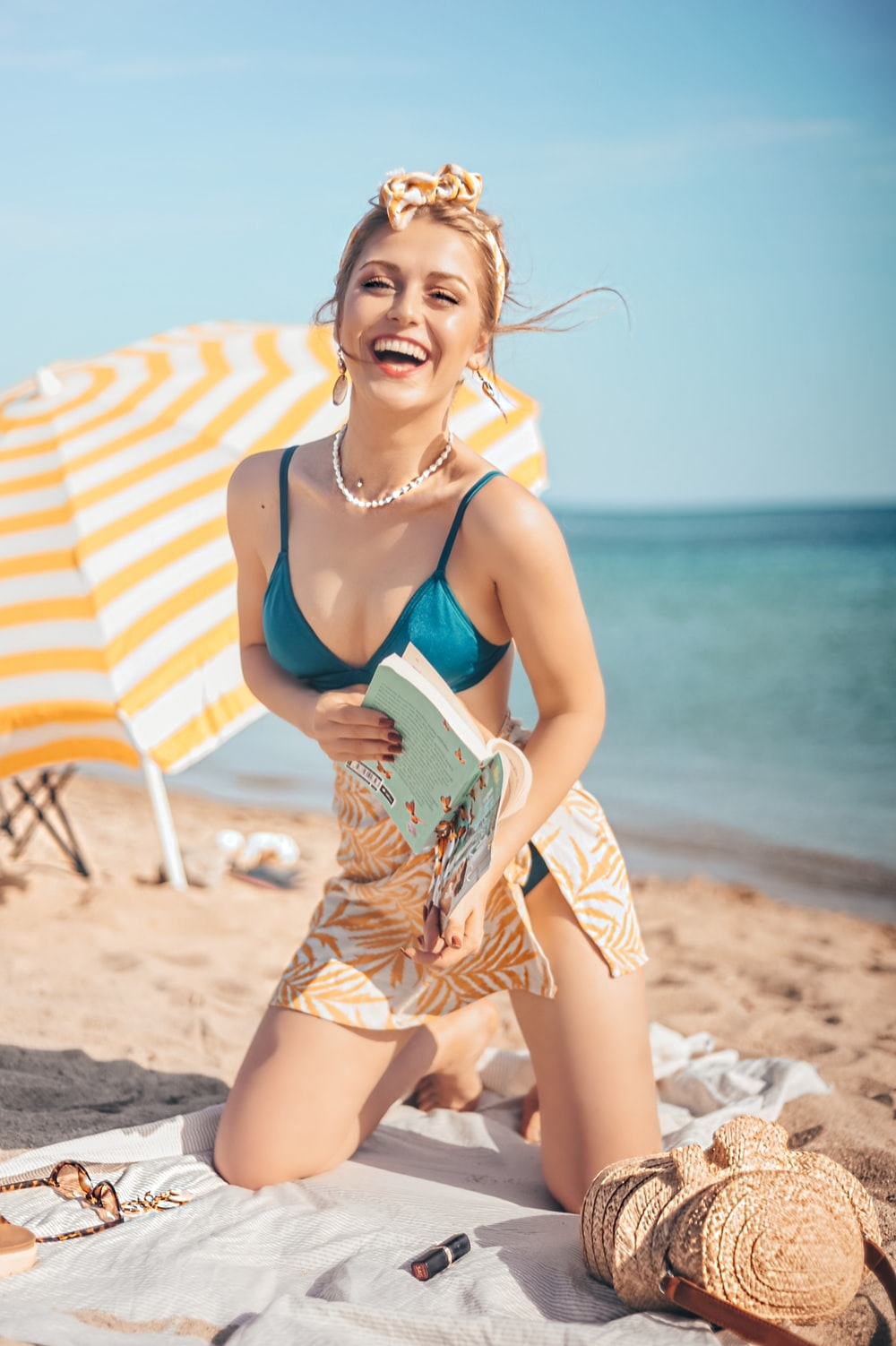 smiling woman in blue brassiere kneeling on white textile on shore during daytime