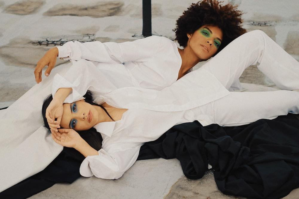 two women laying down wearing white dress shirts