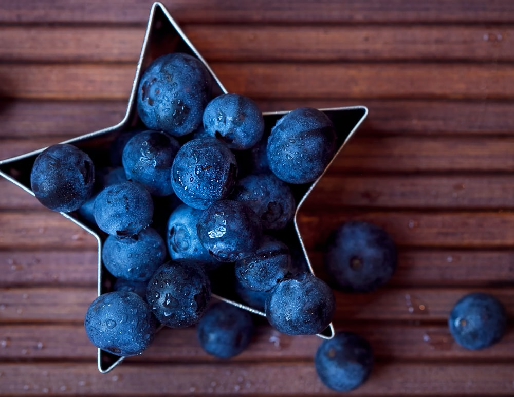 blueberries on wooden surface and in star-shaped bowl