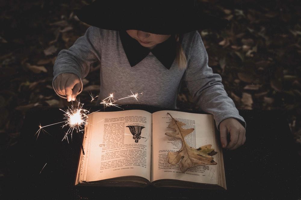 girl holding lighted sparkler while reading book