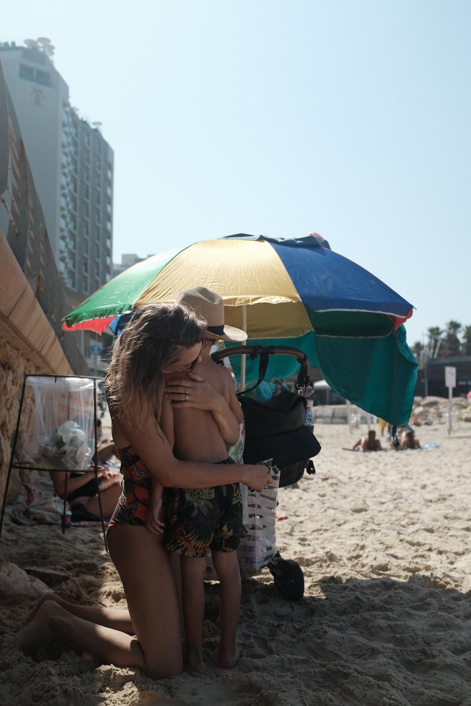 woman hugging boy on shore at daytime
