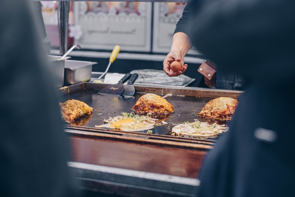 person holding egg near griddle with food