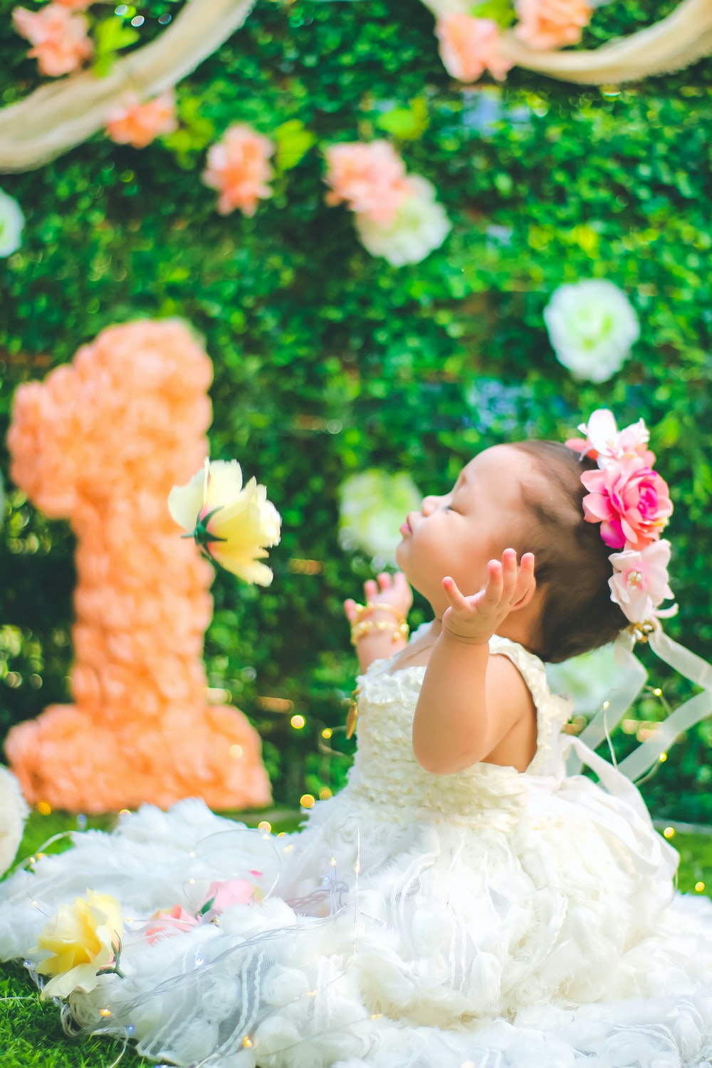 closed eyed baby girl wearing white gown sitting on grass and spreading her arms