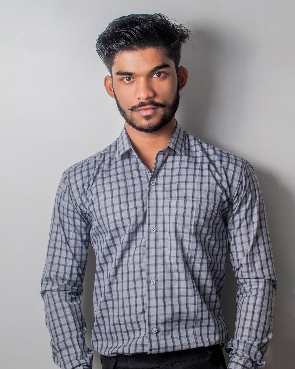 man in gray and black checkered sport shirt and black pants outfit