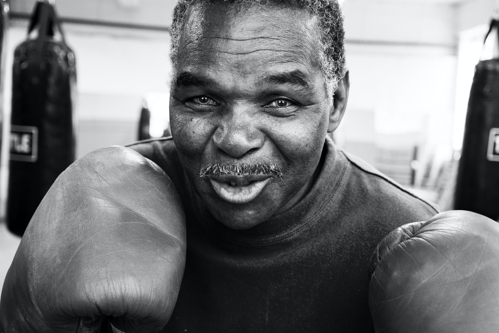 smiling man wearing boxing gloves