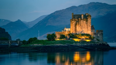 Old scottish castle on small island on a lake at dusk