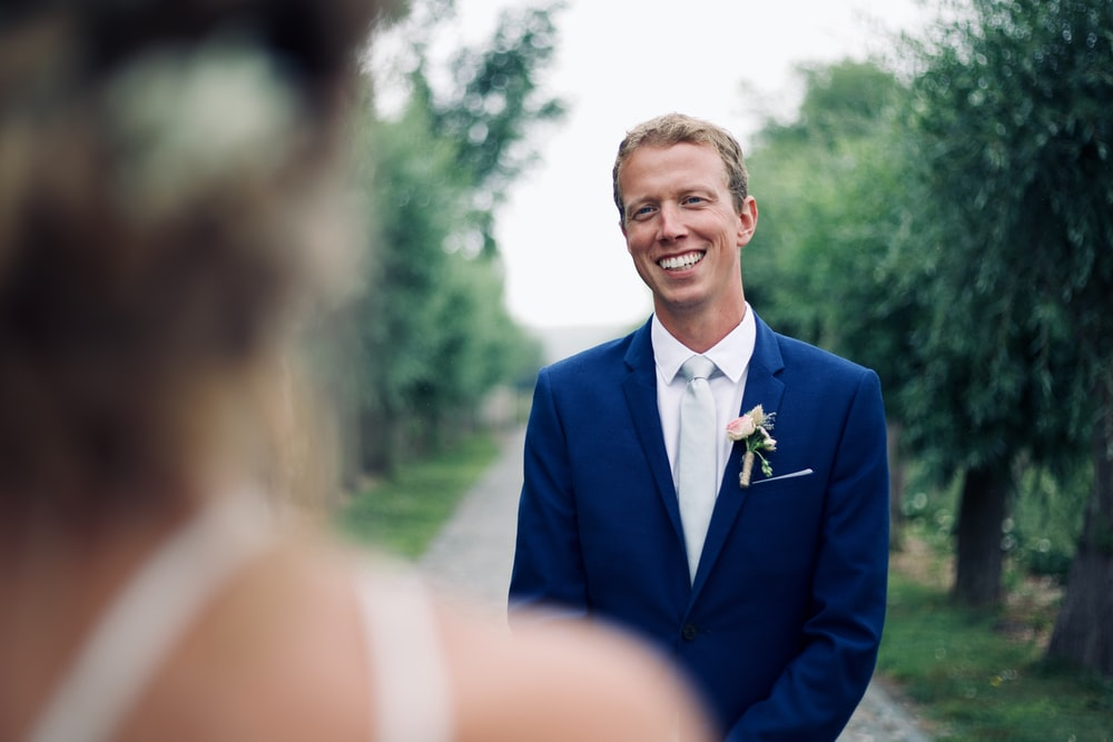 shallow focus photo of man in blue suit jacket