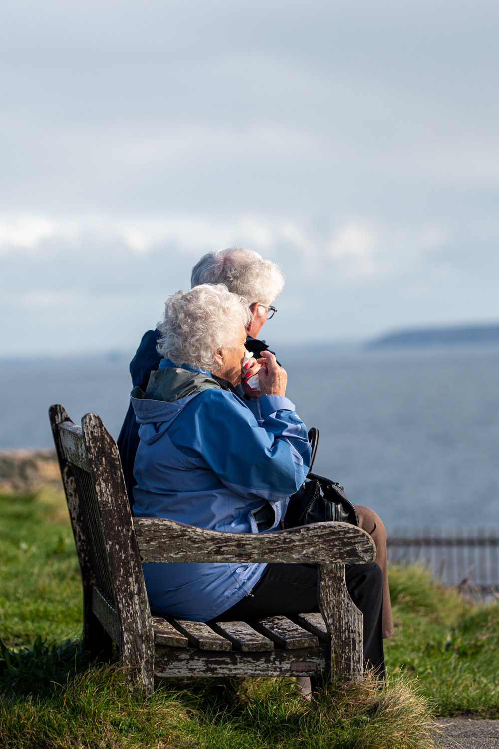 man and woman sitting on gray wooden bench viewing blue sea during daytime