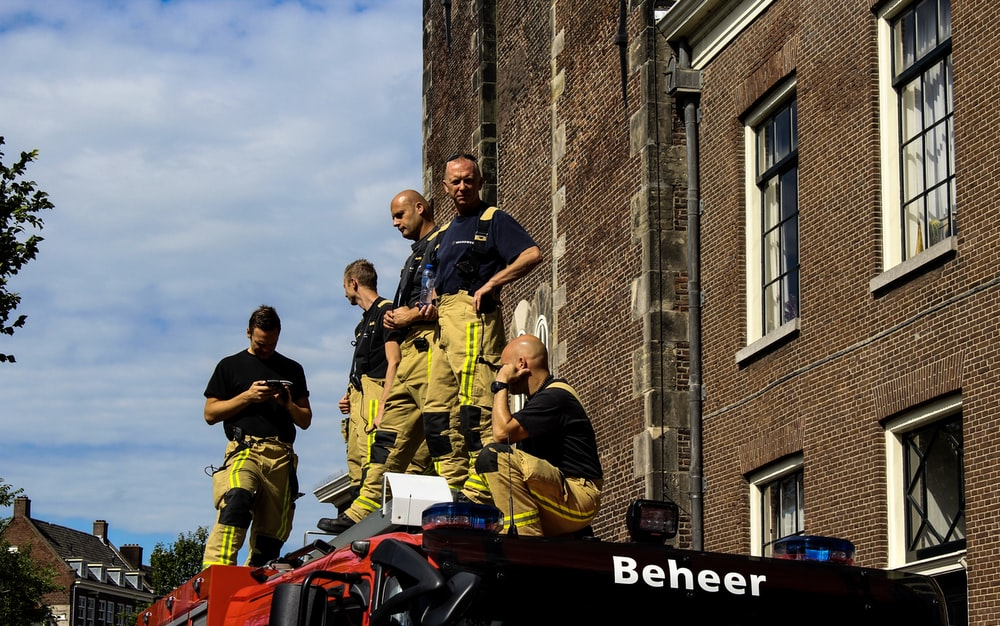 firemen on top of firetruck near brown building under white and blue sky during daytime