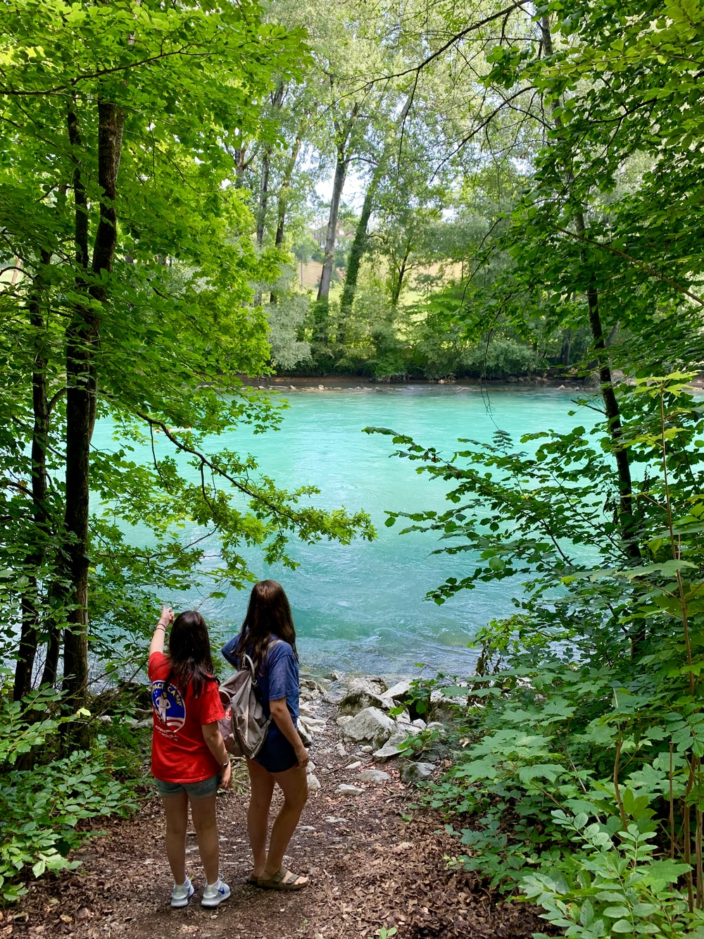 two women standing beside the river under tall trees