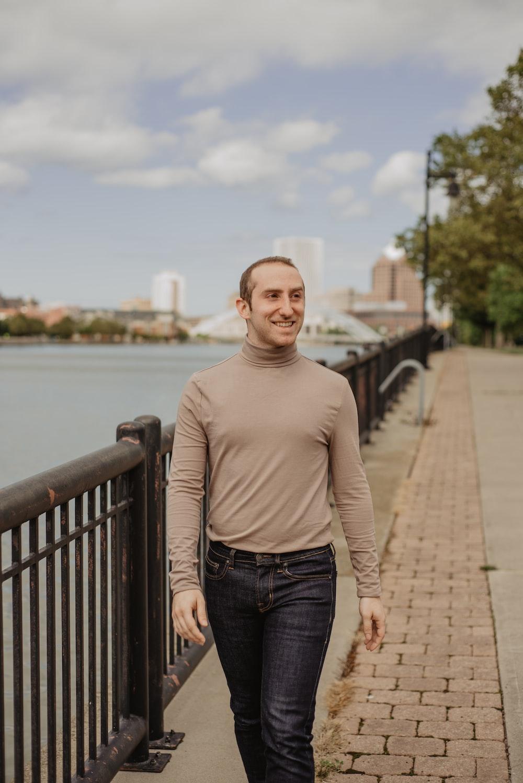 man in gray sweater walking beside body of water