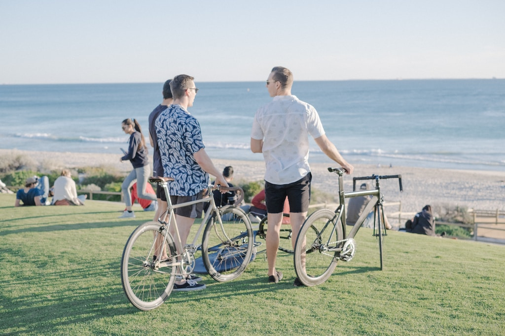 three men with commuter bikes on grass field front of sea