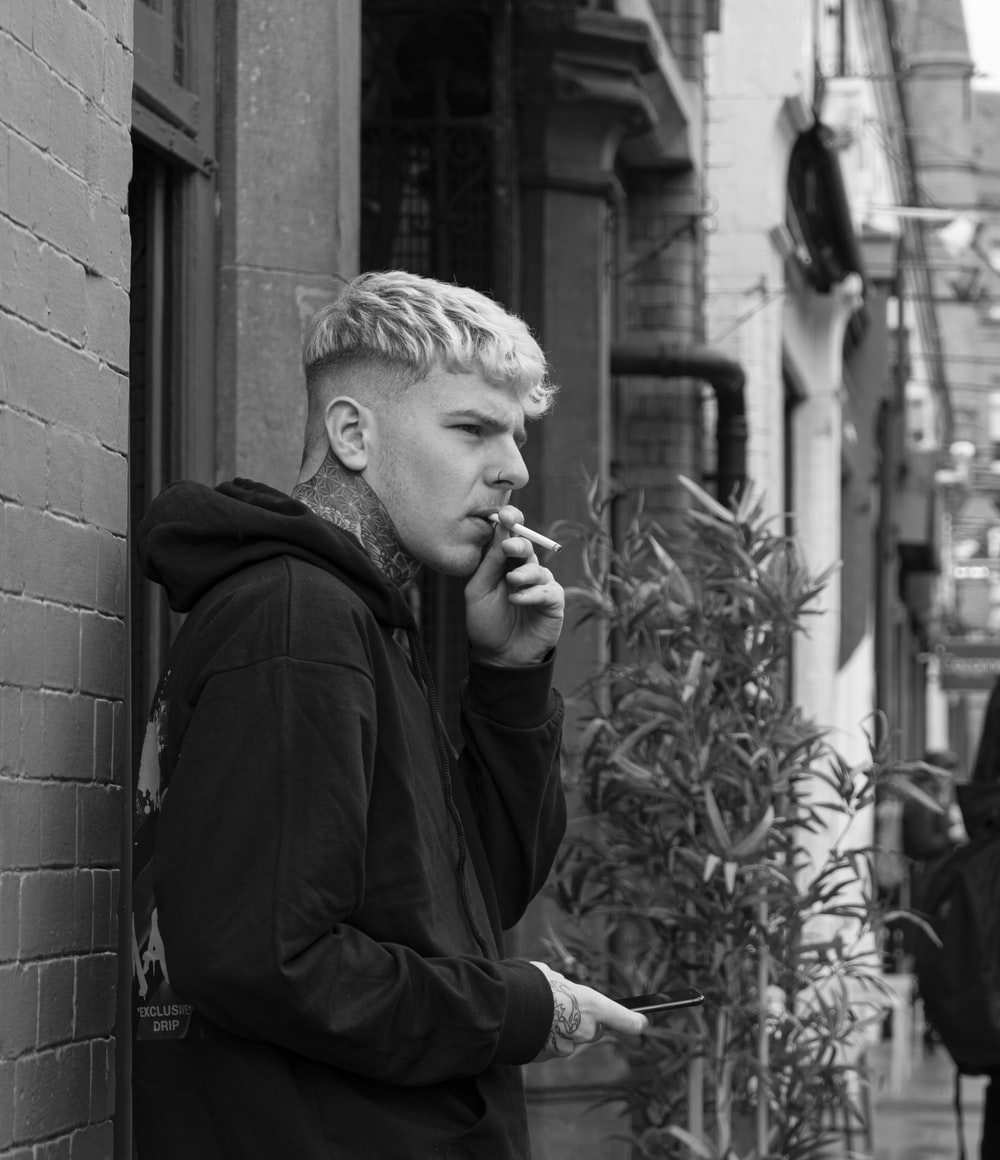grayscale photo of man smoking whiel leaning on brick wall