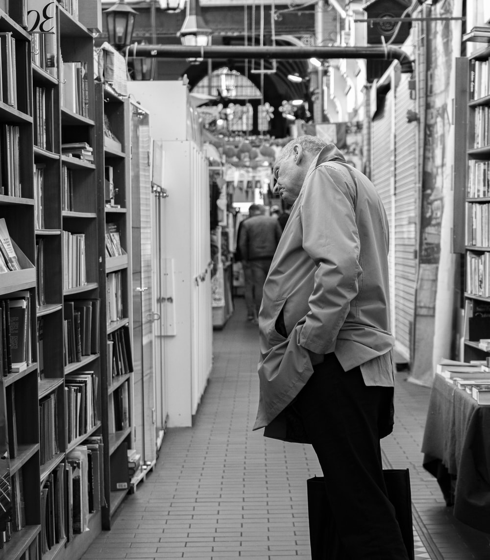grayscale photo of man looking at bookshelves