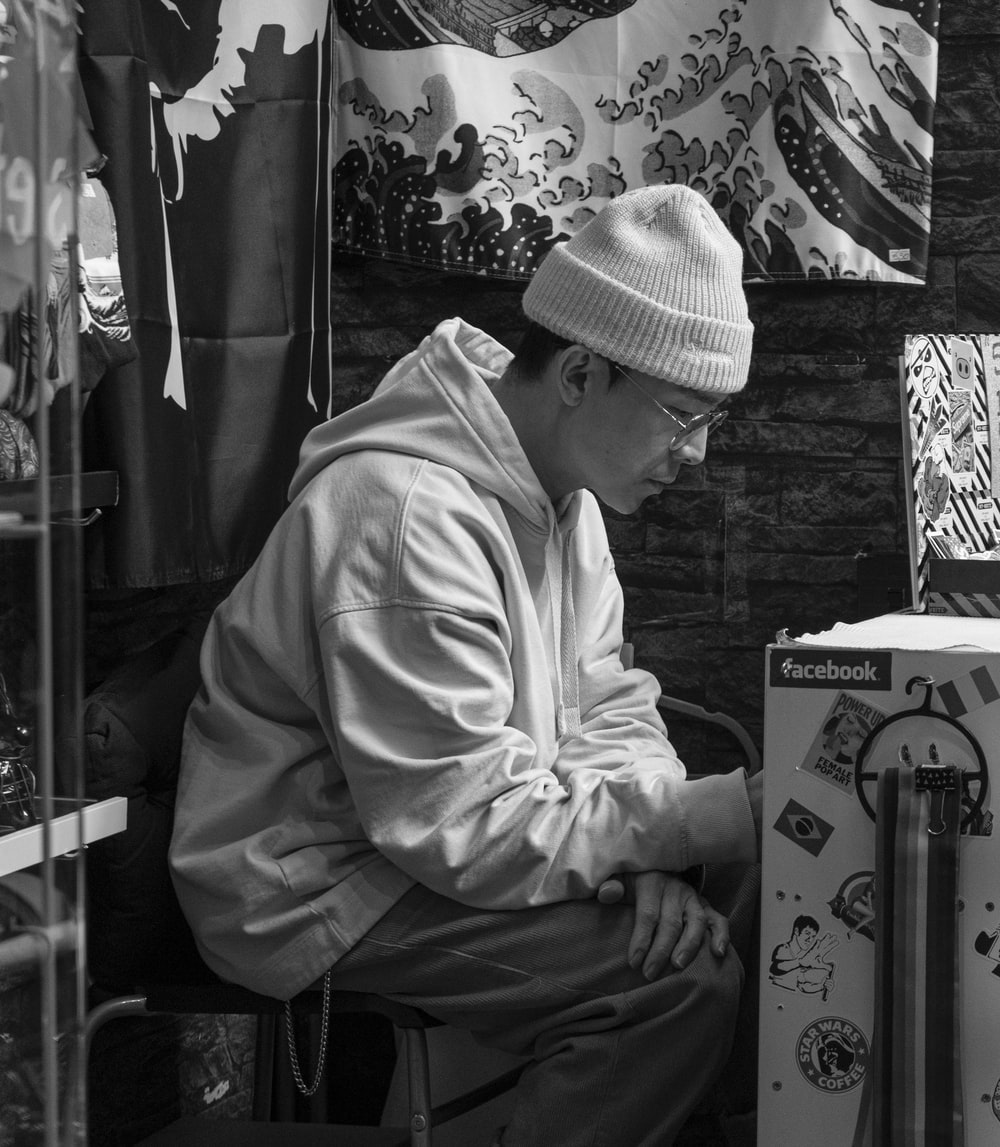grayscale photography of man in hoodie