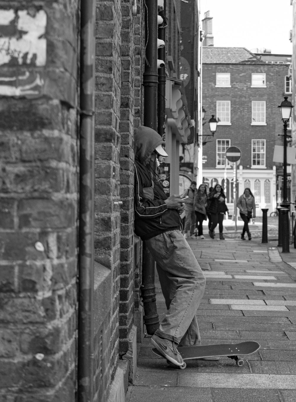 grayscale photo of man with skateboard leaning on wall