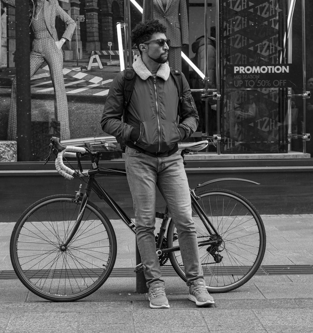 man leaning on bollard near bicycle