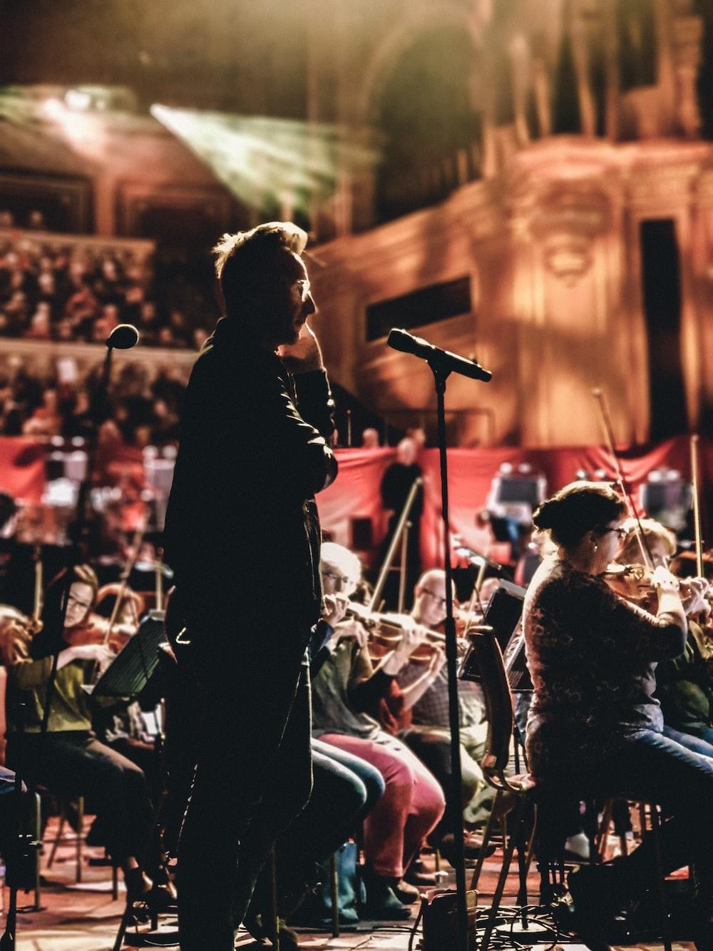 standing man beside choir