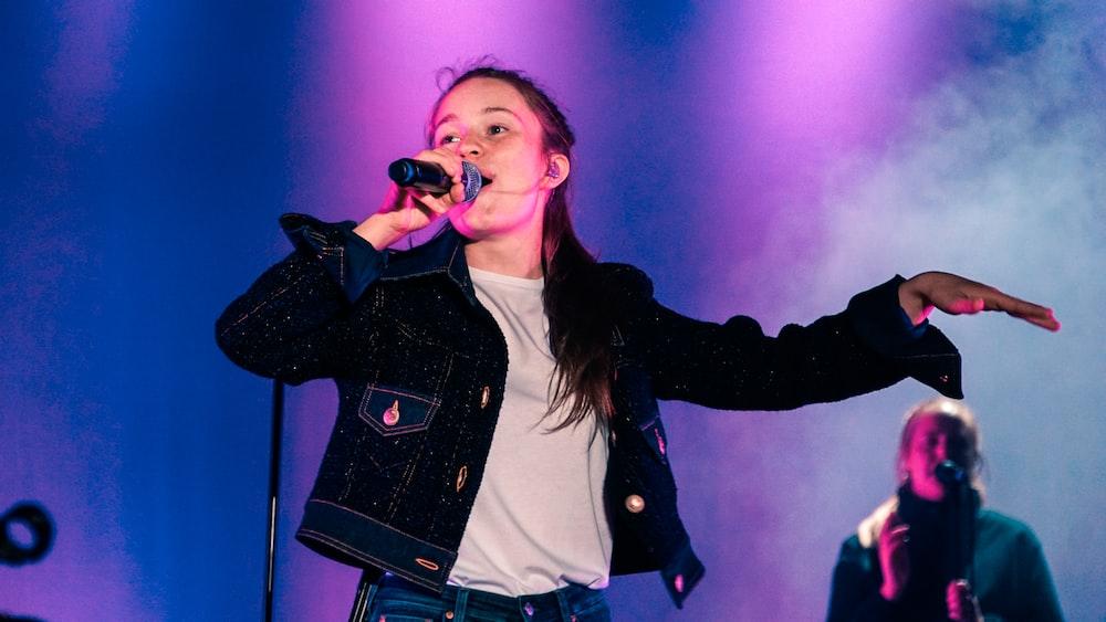 woman wearing black jacket standing and singing