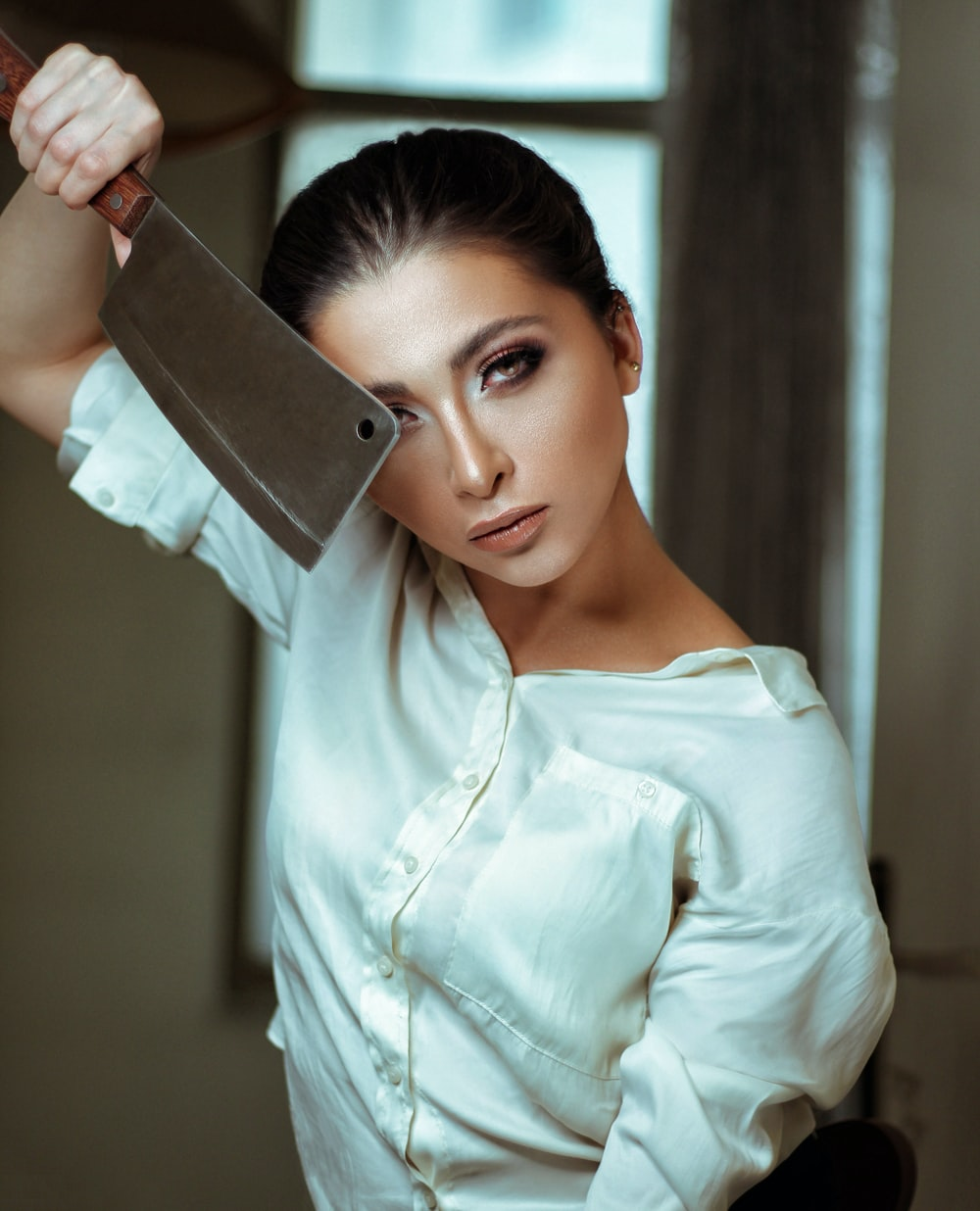 shallow focus photo of woman in white dress shirt holding cleaver