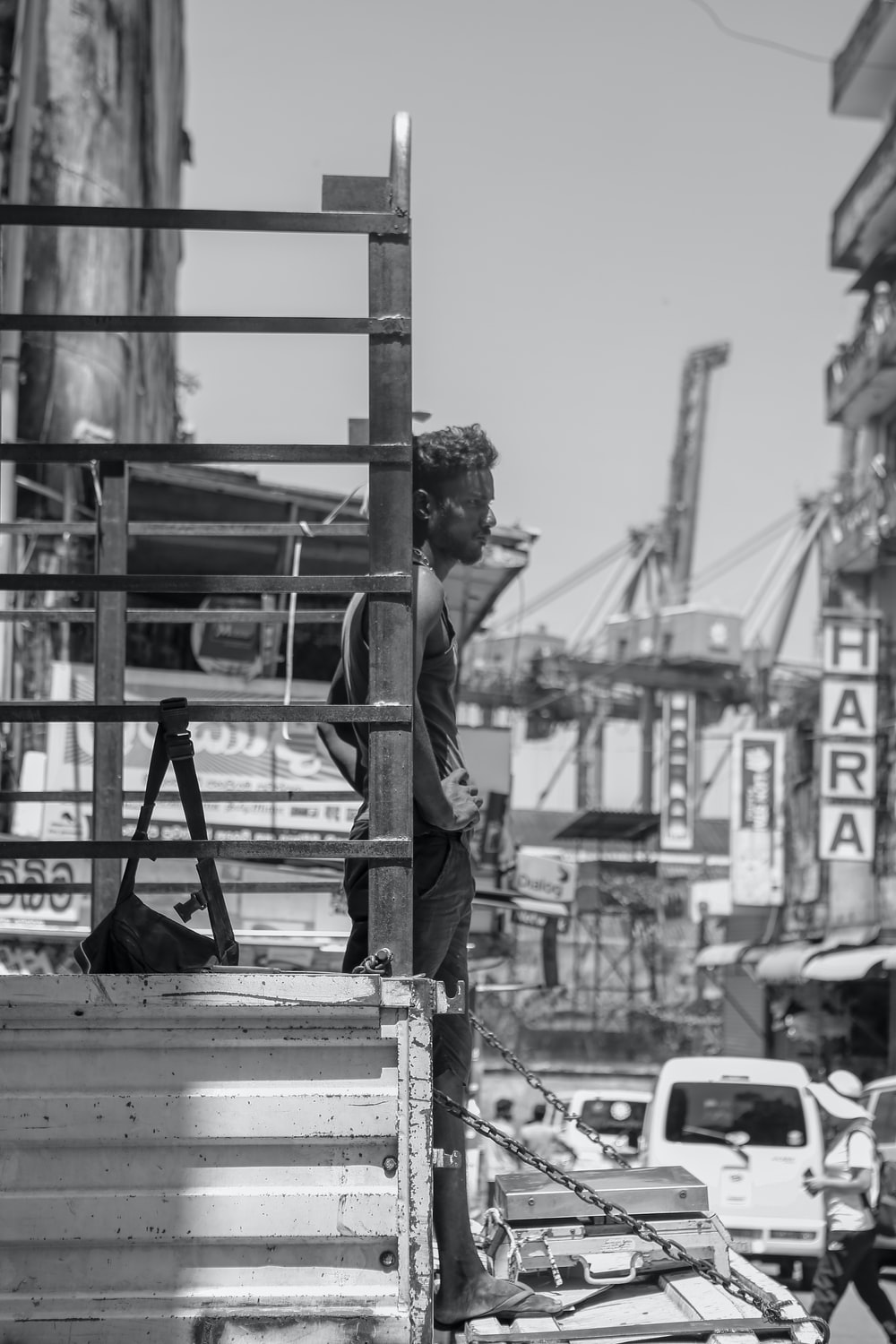 grayscale photography of man standing near post