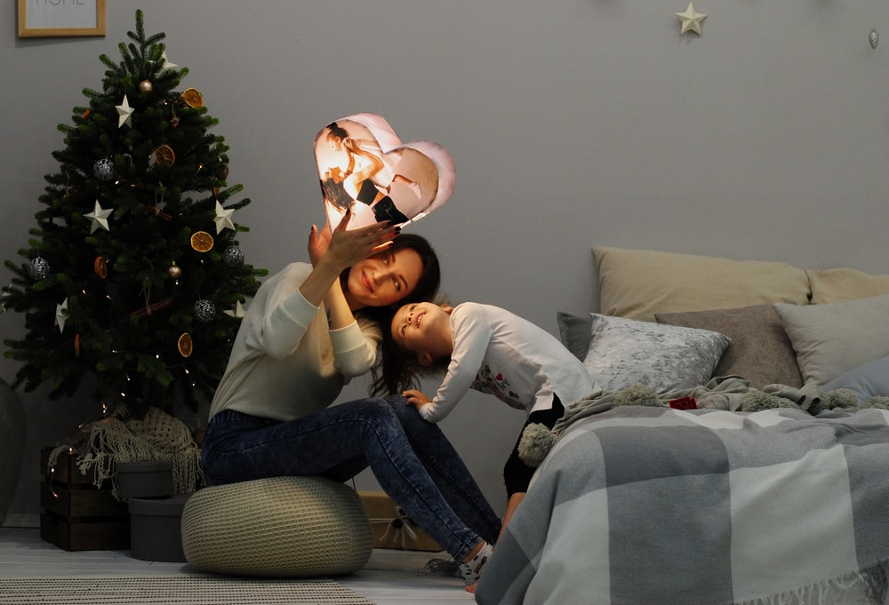 woman by child holding heart lighting decor