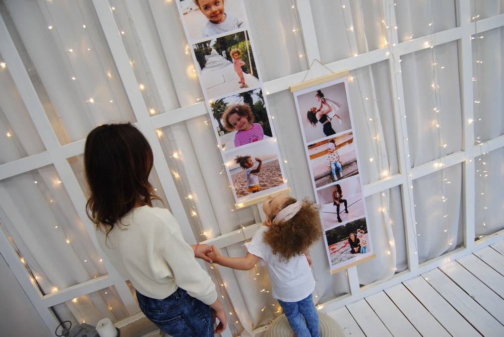 woman and girl looking pictures on wall