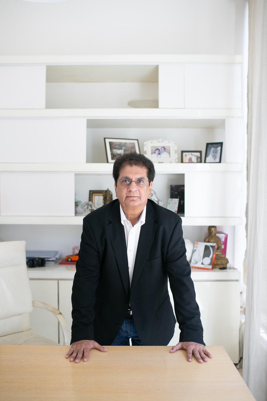 man in black suit standing near white wooden shelf
