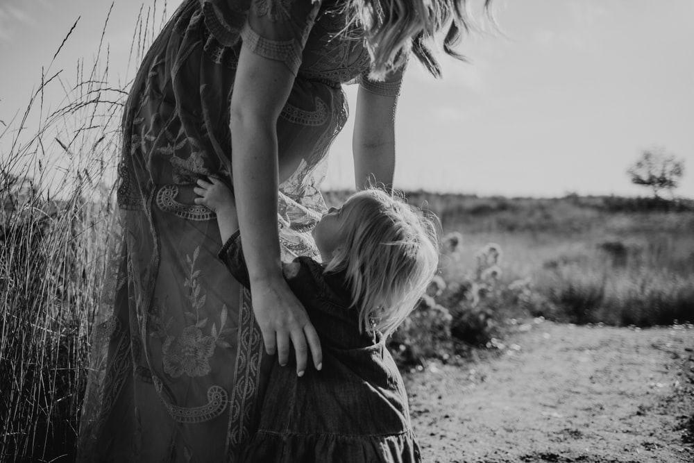 grayscale photography of woman near grass about to carry child