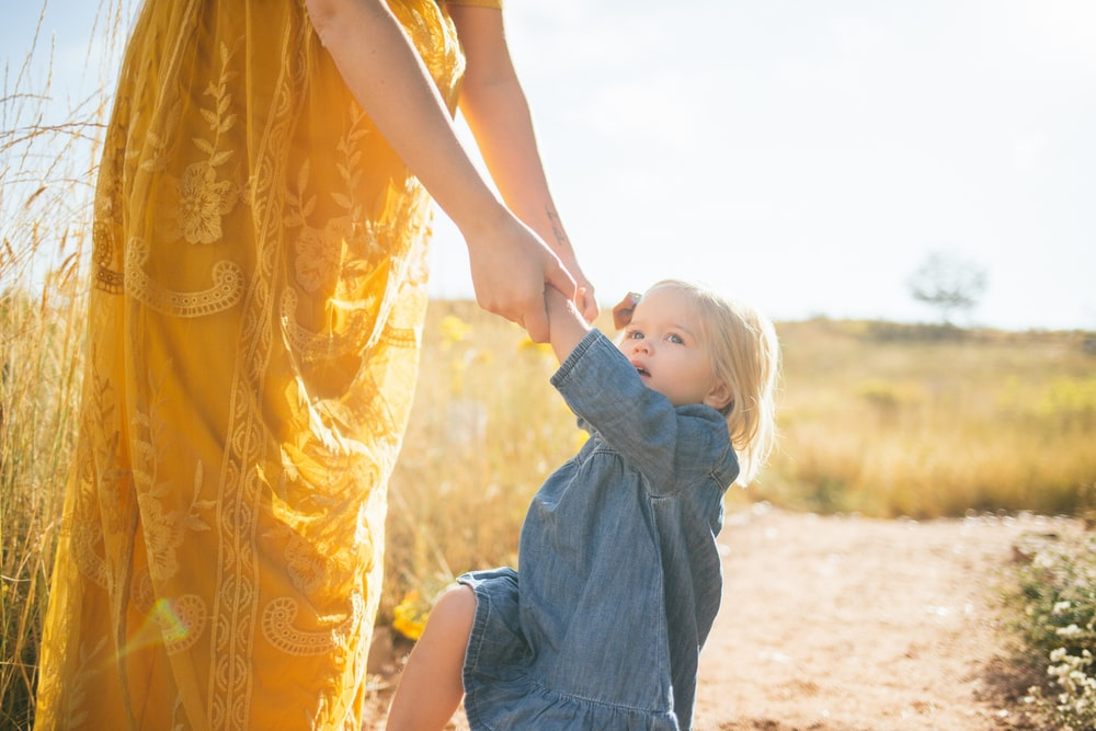 woman wearing yellow dress holding hands of girl during daytime