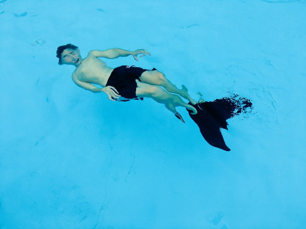 man wearing black shorts and flippers while swimming