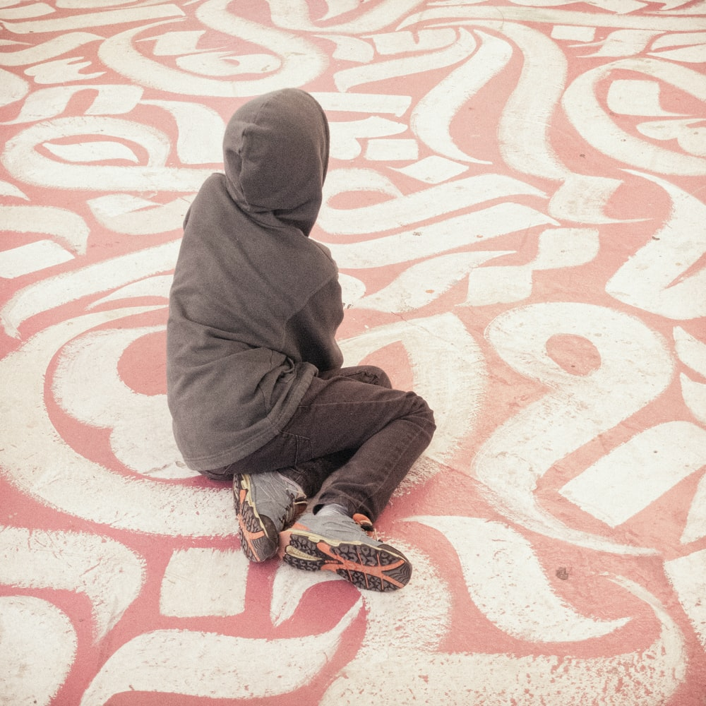 person wearing gray hooded jacket and gray denim jeans sitting on white and pink concrete pavement