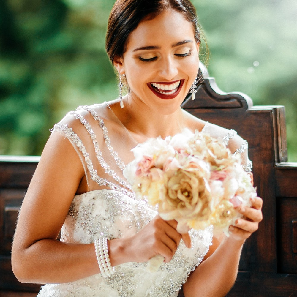 selective focus photo of woman holding bouquet of flower