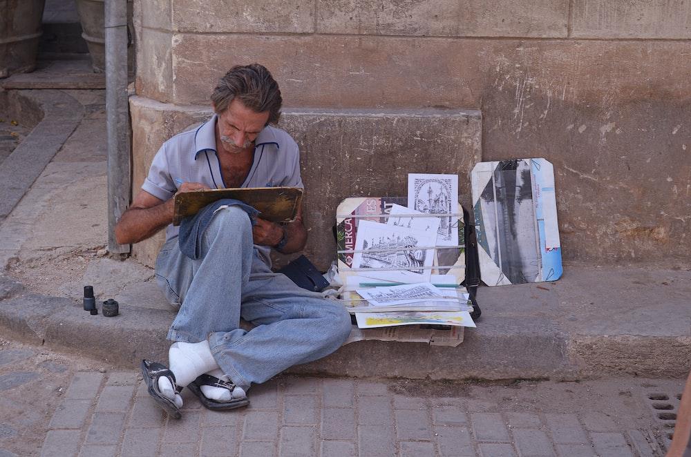 man sitting on sidewalk