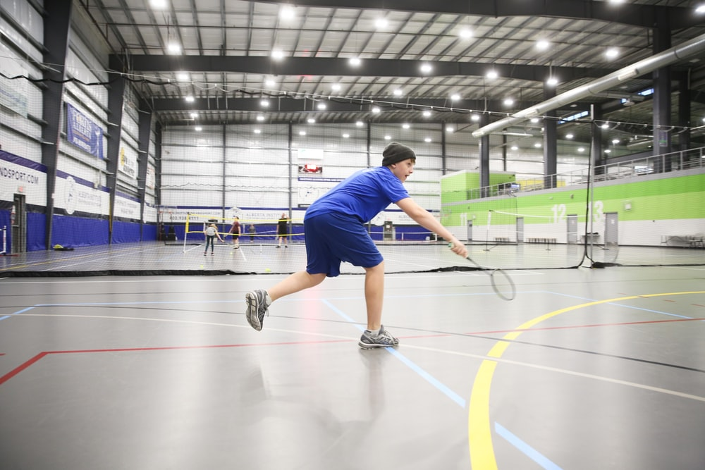man playing badminton inside gymnasium