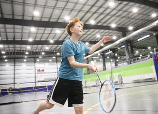 boy in blue crew-neck T-shirt and black shorts playing badminton indoors