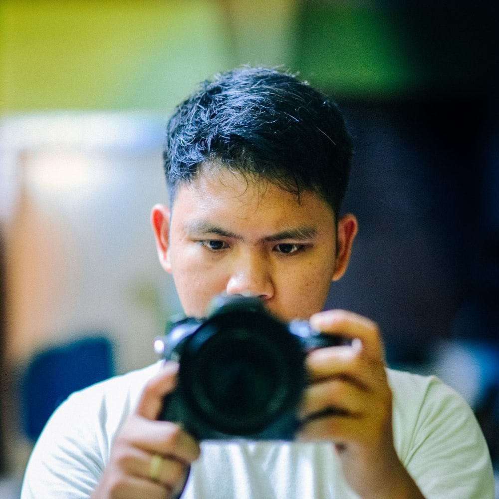 selective focus photography of man holding black camera