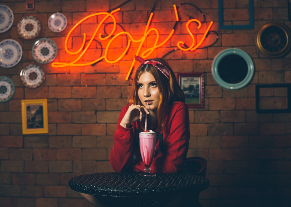 woman sipping drink sitting in front of Bop's neon sign