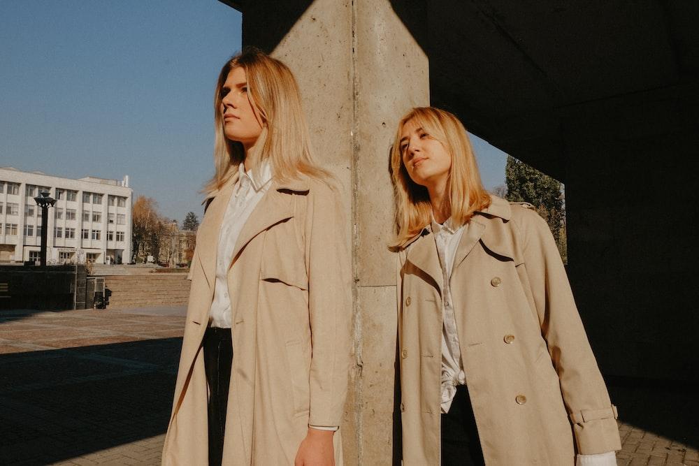 two women wearing brown coat leaning on concrete pillar