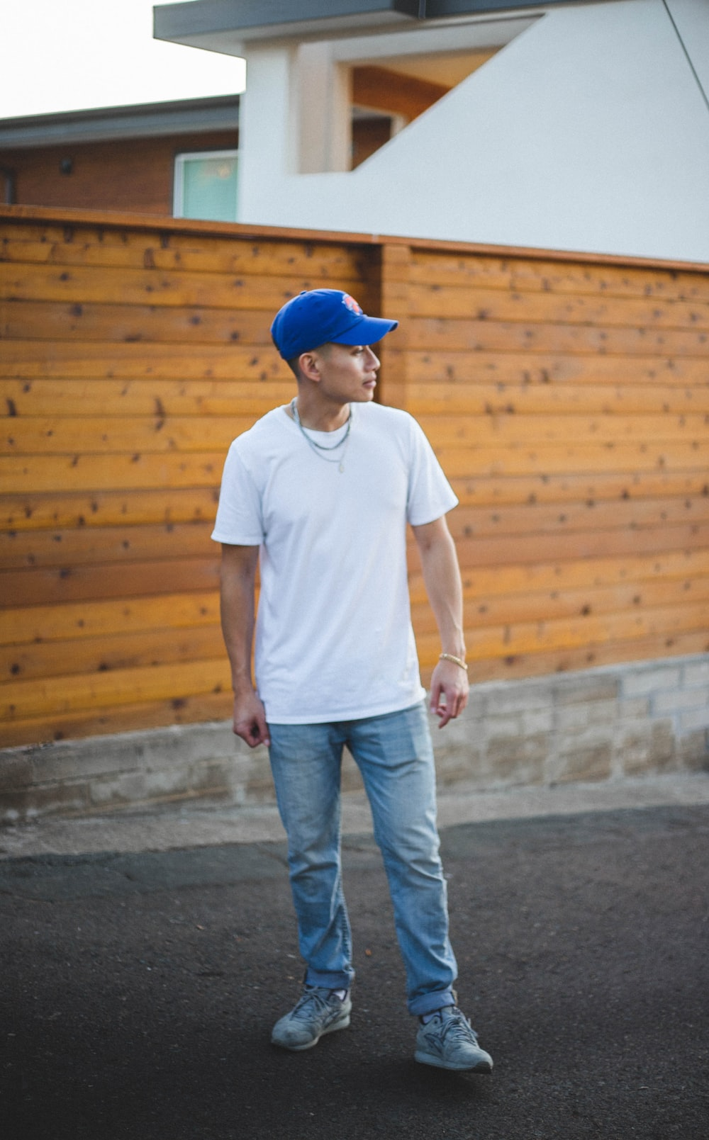 man in white crew neck t-shirt and blue denim jeans standing on gray concrete floor