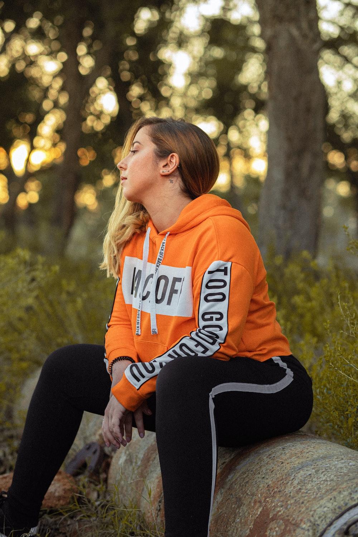 woman sitting on log in over hoodie