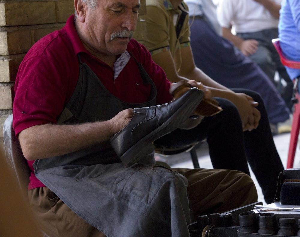 man holding shoe wearing black apron