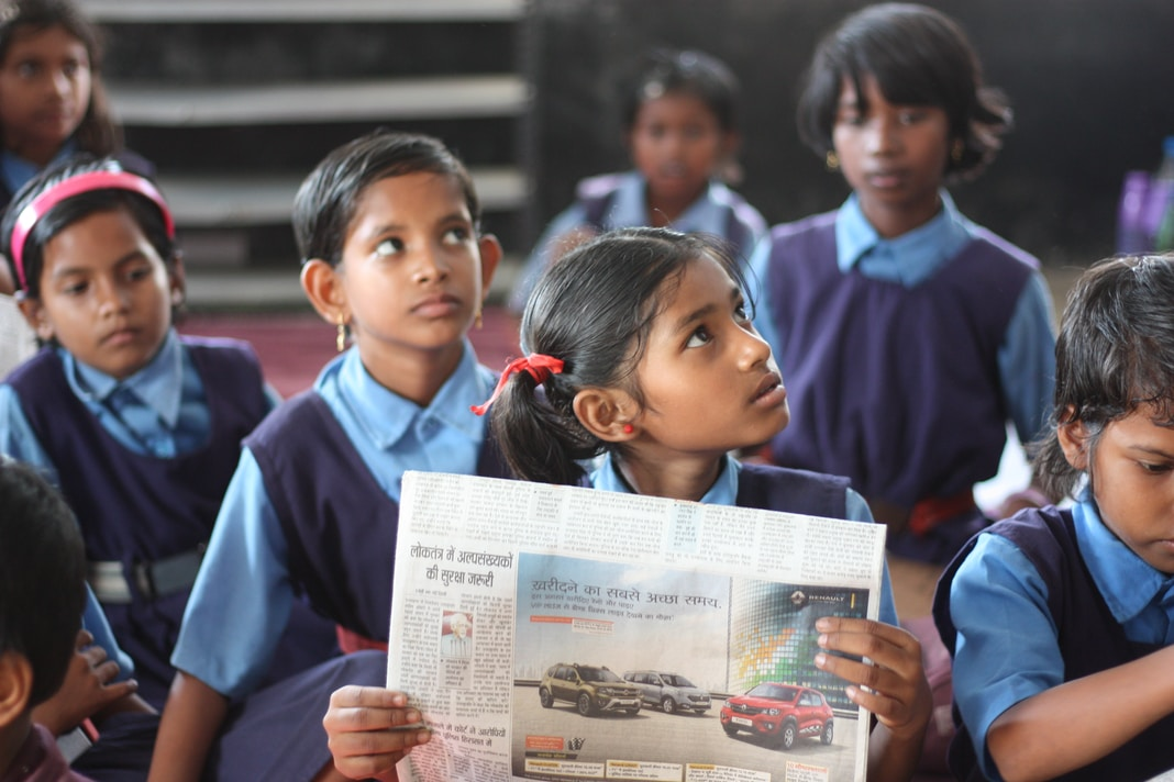 shallow focus photo of girl holding newspaper