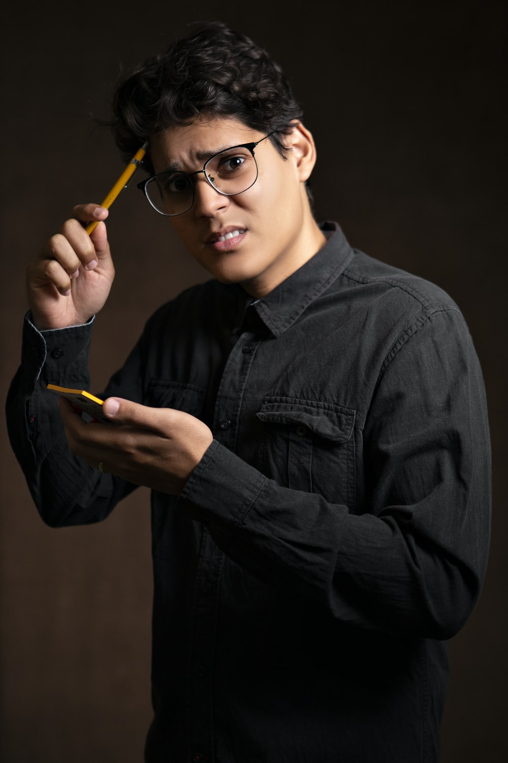 man wearing black denim jacket holding pencil and yellow sticky notes standing while showing confused reaction